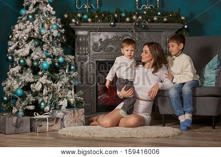 Happy family are sitting near Christmas tree at home. Merry Christmas and Happy New Year. Beautiful young mother with two sons.