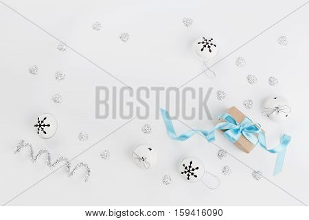 Christmas gift box with blue ribbon and jingle bell on white background from above. Holiday greeting card. Mockup. Flat lay frame.