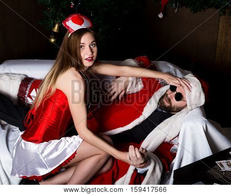 drunk santa claus lying on sofa, female nurse sexy woman in carnival costume, tries to wake him up.