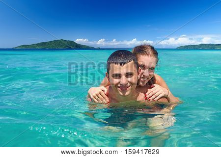 Happy young couple on the tropical beach holiday.