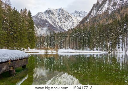 Beautiful And Clear Jezersko Lake With Amazing Mountain Background At Winter
