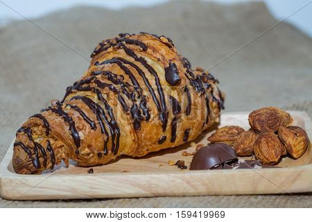 Croissants on a wooden plate  chocolate and almonds. Focus on Croissant macro. The background is blurred out of focus at some point.
