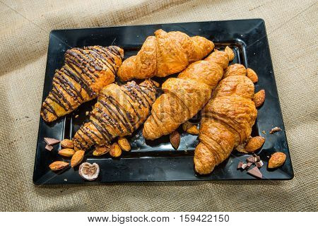 Closeup Croissant on a wide variety of dishes. together chocolate and almonds. Focus on Croissant. The background is blurred out of focus at some point.