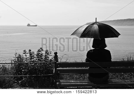 Silhouette of a woman on a bench looking at the sea with feeling lonely