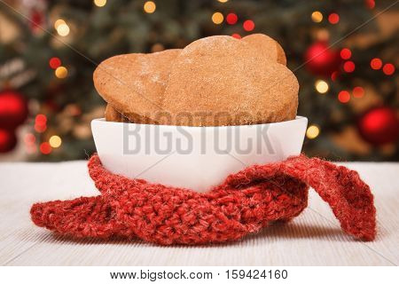 Gingerbreads In White Bowl And Christmas Tree With Lights In Background