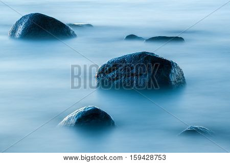 long exposure of blue sea and large stones