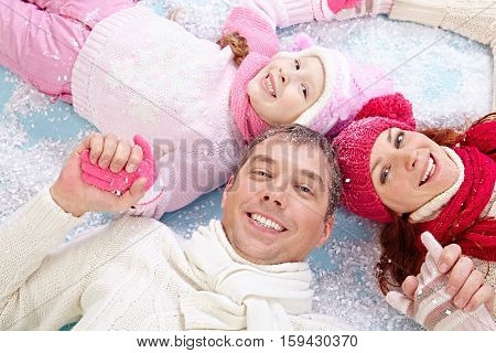 Merry family lying down on snow holding hands