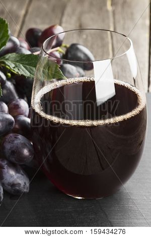 Red Wine And Dark Grapes On A Wooden Background