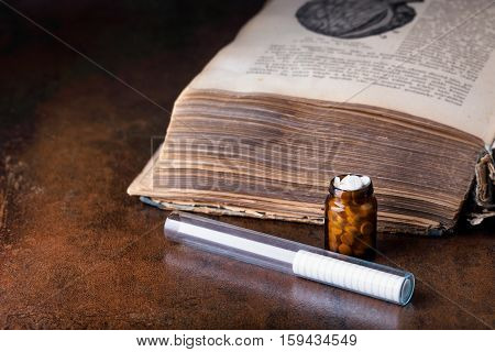 Bunch Of White Pills With Glass Ampoules And Old Medical Book