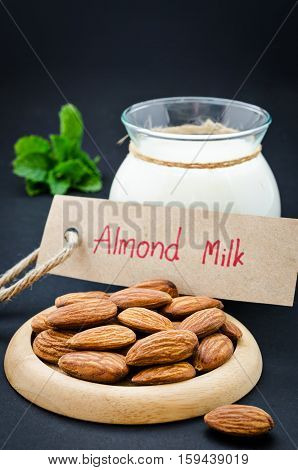 Almond with almond milk in glass with almond milk tag on black background.