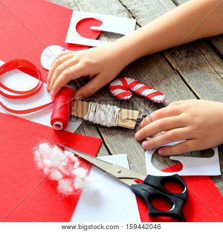 Children hands on old wooden table. Handmade felt Christmas candy ornament, felt sheets and scraps, scissors, red thread, needle, paper template, pins. Baby workplace. Children Christmas art project
