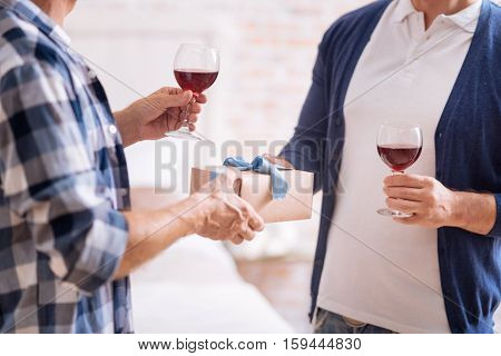 Romantic moment. Cute small romantic box with a gift and two wineglasses in hands of homosexual couple