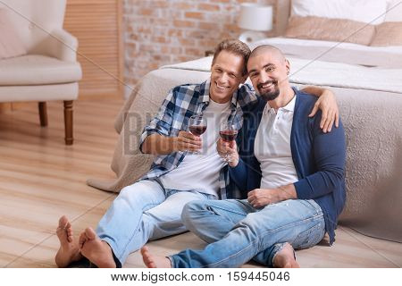 We adore each other. Cheerful delighted positive non-traditional couple sitting on the floor in the bedroom and drinking wine while expressing love and care and hugging each other