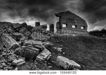 Adobe ruins on a hill against dark skies.