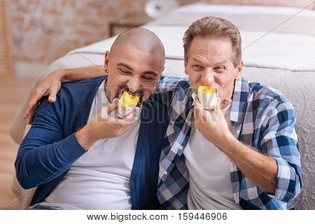 We enjoy our breakfast. Cheerful positive happy non-traditional couple sitting on the floor in the bedroom and eating bakery while expressing happiness