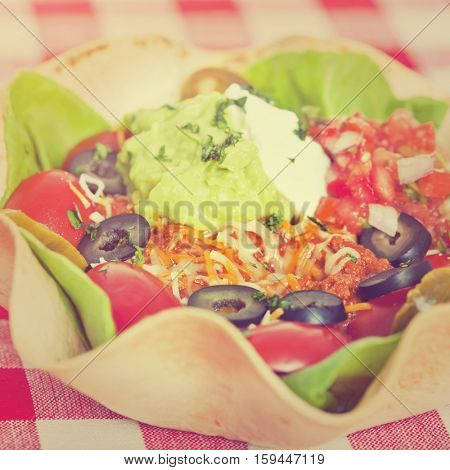 Taco salad in a baked tortilla on a tablecloth