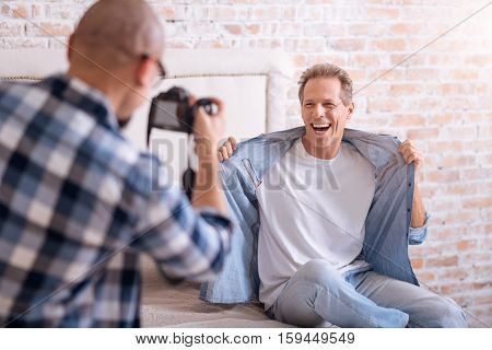 Full of joy . Delighted joyful happy homosexual man sitting on the bed and posing while smiling and his partner taking the picture of him
