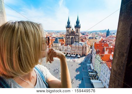 Kostel Panny Marie pred Tynem. Church of the Virgin Mary. A young woman stands on top of the clock tower and looks at the Old Town Square in Prague