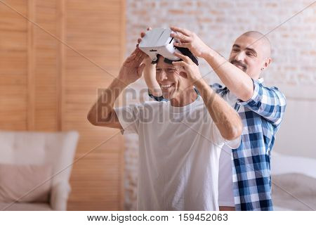 We trying virtual reality. Cheerful smiling delighted friends standing in the bedroom and holding virtual reality glasses while expressing joy and interest
