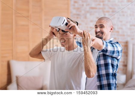 We trying something new. Cheerful happy delighted friends standing at home and wearing virtual reality glasses while expressing joy and interest