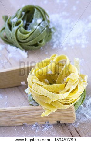 Raw yellow and green pasta on wooden table with flour