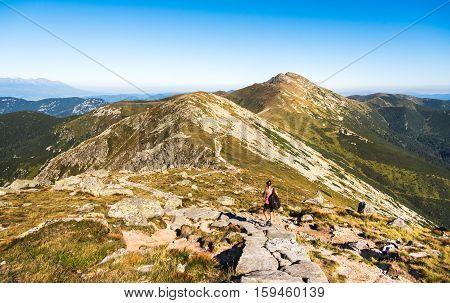 Tourist Goes Downhill along Low Tatras Mountains Ridge in Slovakia. Way to Mount Dumbier.
