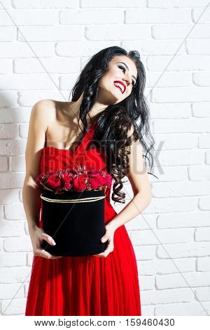 young pretty sexy woman or girl with cute smiling face and long brunette hair has fashionable makeup with red lipstick and dress holds rose flowers bouquet in box on white brick wall background