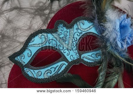 Blue carnival mask with feathers on the red velvet heart