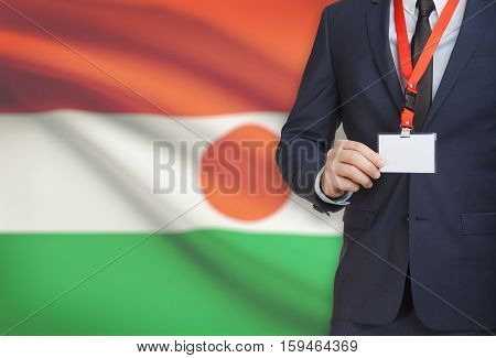 Businessman Holding Name Card Badge On A Lanyard With A National Flag On Background - Niger