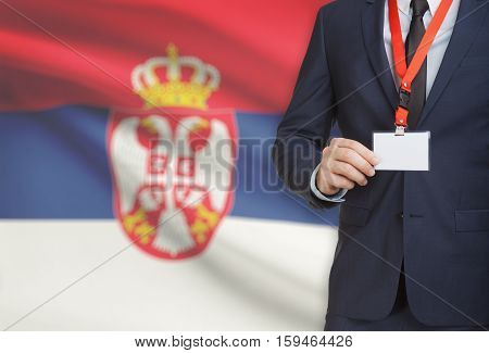 Businessman Holding Name Card Badge On A Lanyard With A National Flag On Background - Serbia