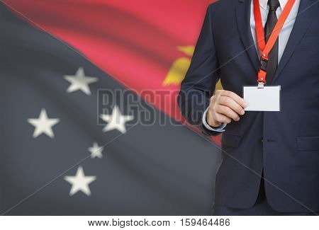 Businessman Holding Name Card Badge On A Lanyard With A National Flag On Background - Papua New Guin