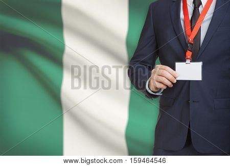 Businessman Holding Name Card Badge On A Lanyard With A National Flag On Background - Nigeria