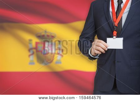 Businessman Holding Name Card Badge On A Lanyard With A National Flag On Background - Spain