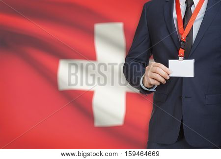 Businessman Holding Name Card Badge On A Lanyard With A National Flag On Background - Switzerland