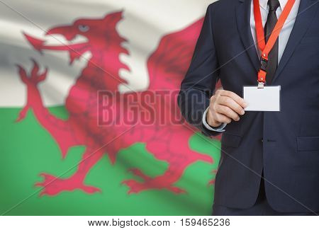 Businessman Holding Name Card Badge On A Lanyard With A National Flag On Background - Wales