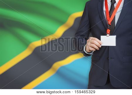 Businessman Holding Name Card Badge On A Lanyard With A National Flag On Background - Tanzania