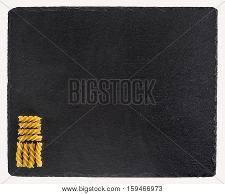 Pasta on a black slate board. Isolated on white background. Top view.