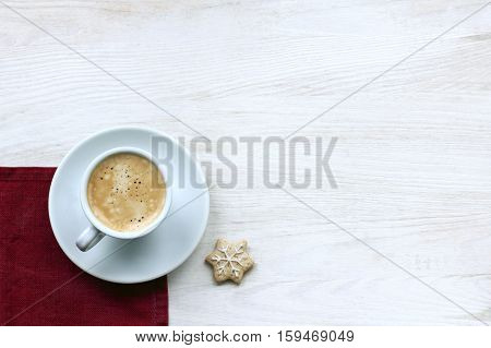frothy espresso in a small cup and ginger snowflake top view / winter coffee break