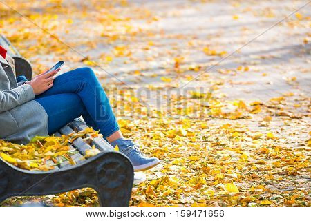 Young Woman Sitting On A Bench In Park