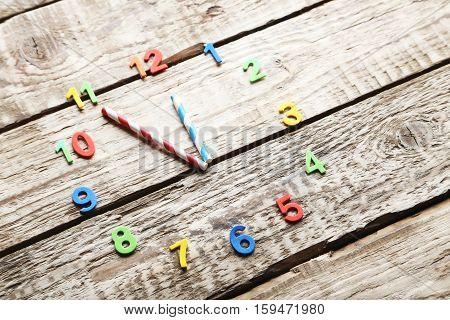 Clock on a grey wooden table, close up