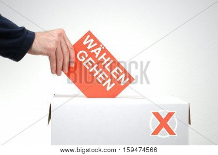 Hand inserting Envelope into Ballot Box - Vote in german language