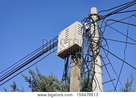 Mess of electric cables and distribution box on a small pylon