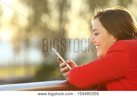 Side view portrait of a girl wearing red jacket checking smart phone on line in winter with a warm light at sunset