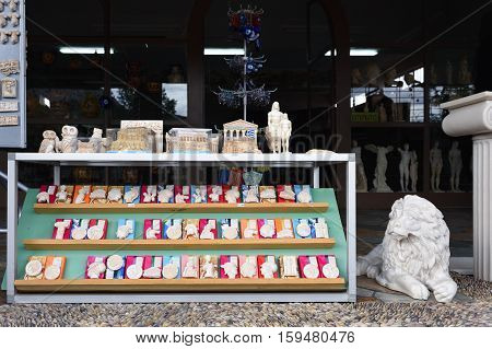 Corinth Greece - Sept 12 2016: Greek souvenir in various form displayed in a small shop on public street. Small statues of ancient heroes and gods the most popular souvenir in Greece
