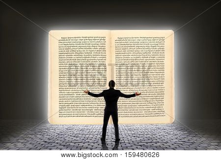 Concept of knowledge. A man in a business suit standing in front of an open book from which pours light. The concept of enlightenment. Wisdom