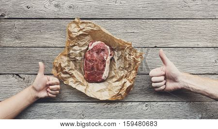 Raw beef steak in craft paper on dark wooden table background, top view with two hands show thumb up. Fresh juicy meat food. Cooking ingredients, butcher's and grocery concept, filtered image