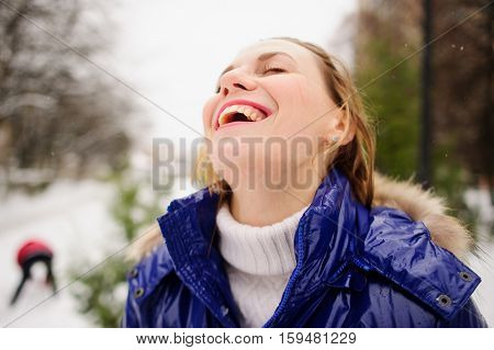 Portrait of young woman against the background a winter landscape. She is dressed in bright blue down-padded coat without headdress. Snowflakes on her hair. Woman has closed eyes and laughs.