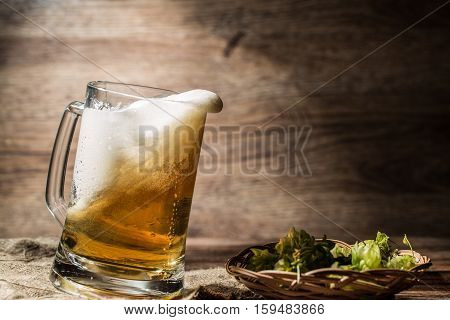 Frothy beer poured from mug standing on linen cloth on empty wooden background
