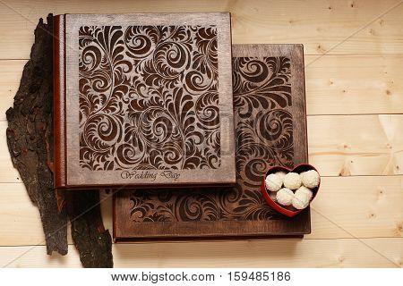 Brown wedding album with photos tree bark and white chocolate coconut candies on vintage wooden background