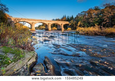Bywell Bridge crosses River Tyne, as it flows through Northumberland, under the stone arched Bywell Road Bridge near Stocksfield